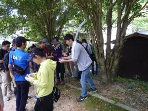 温泉の源泉横で学生が参加者にスタンプ押し