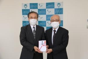 中村信悟同窓会長から山村重彰理事長に目録が贈呈されました